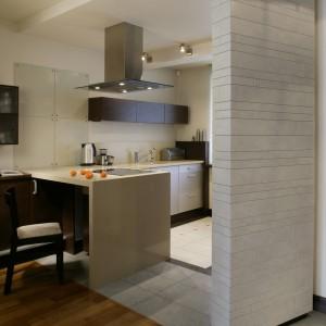 Za ścianą obłożoną płytkami znajduje się przestrzeń kuchni. Zabieg ustawienia jej pod lekkim skosem sprawił, że wskazuje jednocześnie drogę do salonu. Fot. Bartosz Jarosz.