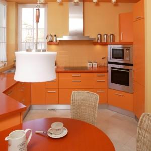 Kuchnię spowijają pomarańczowo-żółte odcienie. Formy detali - jak lampki na suficie czy dekoracja okien -  nawiązują do stylowych wnętrz rezydencji. Fot. Bartosz Jarosz.