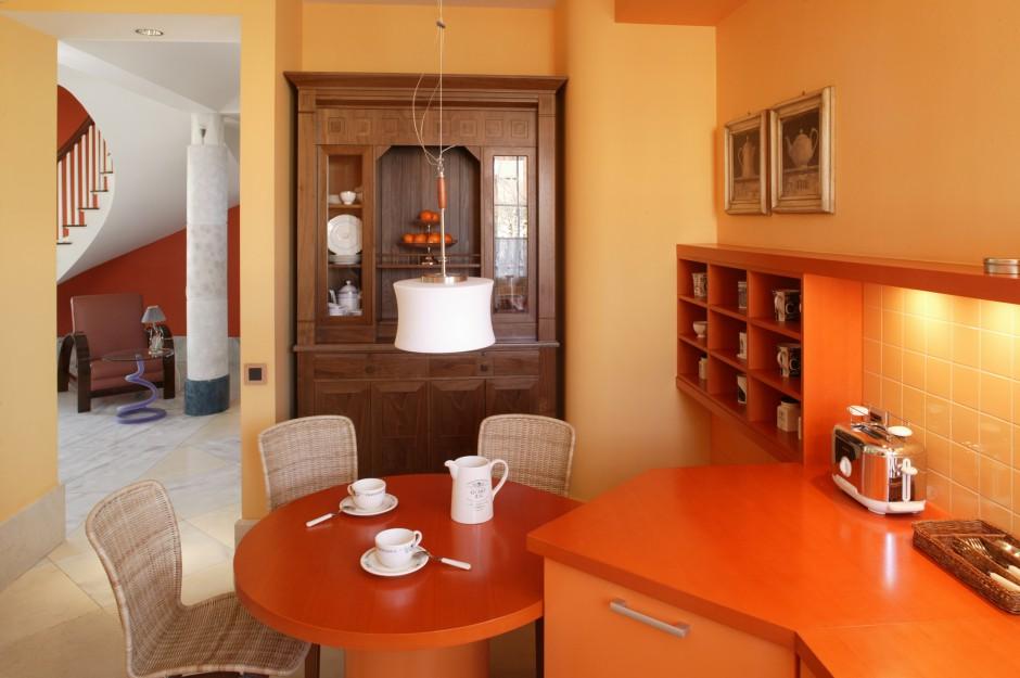 Okrągły stolik śniadaniowy i  krzesła rozpoczynają kuchenną zabudowę. Z reprezentacyjnej jadalni widoczne są stylowy kredens i półki na porcelanę.  Fot. Bartosz Jarosz.
