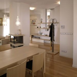 Widok z kuchni na salon i przedpokój. Dzięki podobnej stylistyce, wszystkie strefy funkcjonalne wzajemnie się przenikają, wprowadzając ład i harmonię do części dziennej mieszkania. Fot. Monika Filipiuk.