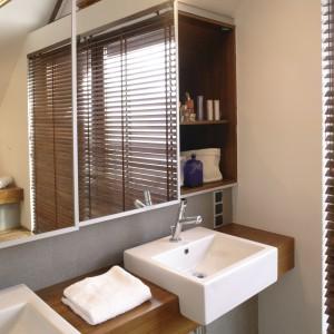 Ścianę nad umywalkami zdobią lustra, które optycznie powiększają przestrzeń łazienki. Za przesuwanymi taflami ukryte są praktyczne szafki, oddzielne dla pani i pana domu. Fot. Monika Filipiuk.