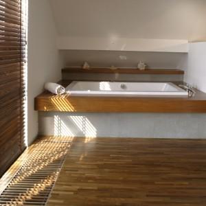 W salonie kąpielowym w bardzo praktyczny sposób wykorzystano skosy poddasza, ustawiając pod nimi wannę. Wokół niej zamontowano drewniany postument. Fot. Monika Filipiuk.