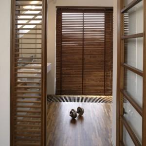 W pomieszczeniu zastosowano powtarzalność drewnianych elementów – podłoga pokryta mozaiką, wanna ozdobiona obramowaniem, półeczki na bibeloty pod sufitem. Fot. Monika Filipiuk.
