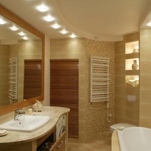 Drewno jest idealnym dopełnieniem aranżacji, której przyświeca efekt przytulności. Drewniana jest rama lustra i roleta zasłaniająca piec. Fronty szafek, choć wykonane z laminatu – doskonale imitują drewno. Fot. Monika Filipiuk.