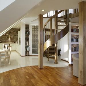 Zaokrąglony kształt ściany z pustaków szklanych jest świadomym nawiązaniem do spiralnej formy schodów i linii na podłodze. Skosy sufitów i nieregularne ściany dopełniają wrażenie dynamicznego charakteru całości. Fot. Monika Filipiuk.