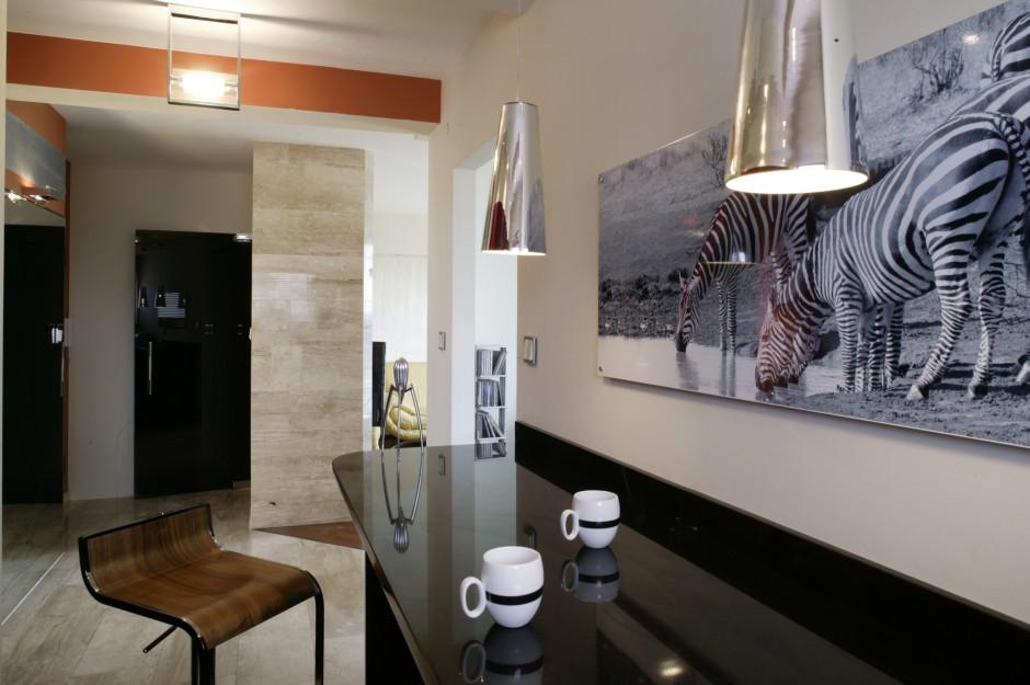 Domownicy najczęściej jedzą posiłki w kuchni. Na ścianie przy granitowym blacie jadalnianym (blat został podwyższony, co zwiększyło komfort siedzenia), umieścili powiększone zdjęcie zebry, wykonane przez właścicielkę podczas safari w Kenii. Fot. Monika Filipiuk.