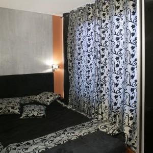 Srebrny pas na ścianie, o takiej samej szerokości co łóżko, utworzył efektowne przedłużenie wezgłowia. Po jego obu stronach umieszczono bliźniacze lampy wydobywające metaliczny blask elementu dekoracyjnego. Fot. Monika Filipiuk.