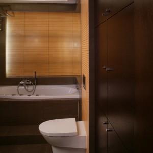 Spokojne brązy płytek ceramicznych i drewna wenge już od wejścia zapraszają w świat relaksu i wyciszenia. Szafki wbudowane w ścianę służą do przechowywania drobiazgów. Fot. Monika Filipiuk.