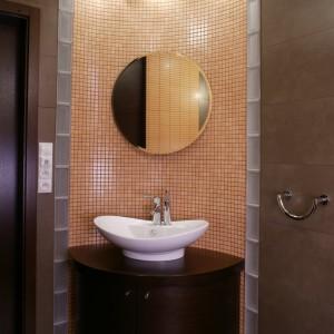 Wyokrąglony fragment ściany otula umywalkę. Pionowe pasy pustaków szklanych po bokach pozwalają przenikać światłu. Fot. Monika Filipiuk.
