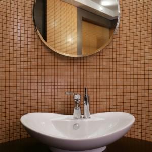 Fantazyjną linię umywalki podkreśla żółty kolor mozaiki. Okrągłe lustro z fazowanymi krawędziami dopełnia całości. Fot. Monika Filipiuk.