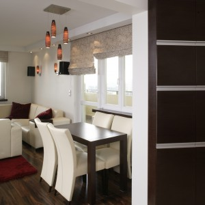 Jadalnia znajduje się tuż przy kuchni, ale już w przestrzeni salonu. Zastosowano tutaj tę samą kolorystykę, a czerwone dodatki – dywan, poduszki, klosze lamp – dynamizują aranżację. Fot. Bartosz Jarosz.