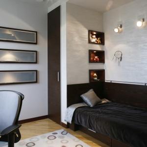 Na ścianie przy łóżku (projekt architektki,) pokrytej metaliczną strukturą, zamontowano trzy kinkiety. Fot. Monika Filipiuk.