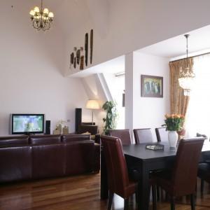 Duży jadalniany stół jest rozkładany. Krzesła tapicerowane brązową skórą zdobią wyraźne przeszycia wokół siedzisk i oparć. Podłogę w salonie  i jadalni pokrywają deski z drewna merbau. Fot. Monika Filipiuk.