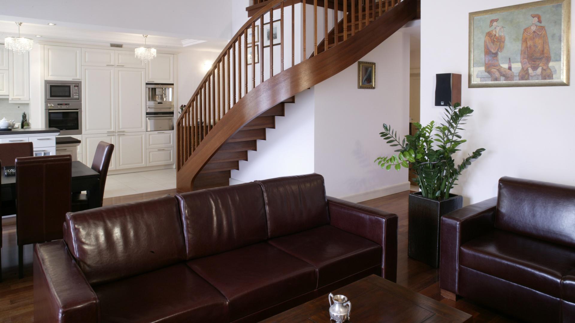 W kuchni, w odróżnieniu od jadalni i salonu, dominują jasne barwy. Wiodące na antresolę schody zostały wykonane na zamówienie z drewna merbau. Fot. Monika Filipiuk.