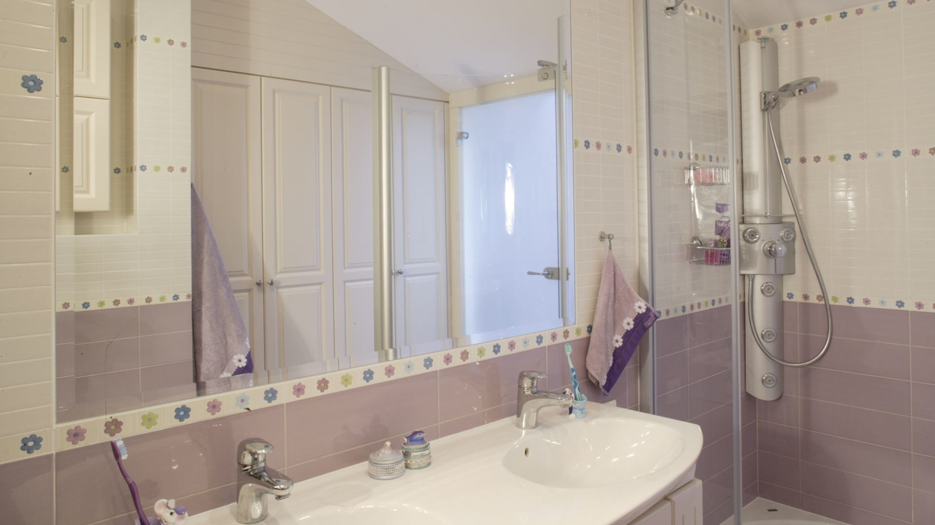 Podwójna umywalka pochodzi z oferty firmy Koło. Panel prysznicowo-masażowy firmy Hansgrohe jest wyposażony w specjalny termostat, który zapobiega ewentualnemu oparzeniu się przez dzieci. Fot. Monika Filipiuk.