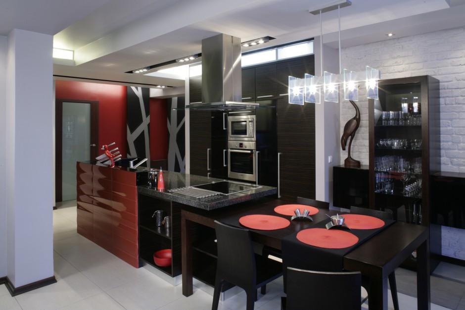 Czerwone i czarne. Efektowna, połączona z jadalnią kuchnia, to domowe centrum, w którym zwykle toczy się życie rodziny. Na pierwszym planie – stół z barwionego na wenge dębu i komplet krzeseł (Natuzzi). Fot. Monika Filipiuk.