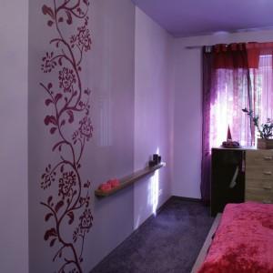 Sypialniana oranżeria... Dekoracyjny wzór na ścianie został odwzorowany z kwiatowego motywu, występującego na półprzejrzystych zasłonkach. Fot. Monika Filipiuk.
