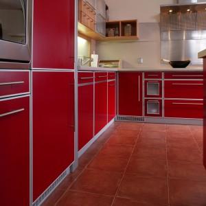 Perfekcyjnie przemyślane dzieło to detale, które składają się na obraz całości. Na jasnej ścianie czerwona, poprzecinana stalowymi elementami zabudowa kuchenna o charakterze użytkowym. Fot. Tomasz Markowski.