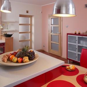 Na ścianie w odcieniu rozbielonej czerwieni, nie tylko kolory, ale także proporcje zostały zamienione. Tym razem w czerwonej ramie, lekkie, z matowego szkła ze stalową opaską prostokąty tworzą nowoczesny kredens, pełniący przede wszystkim funkcje dekoracyjne. Fot. Tomasz Markowski.