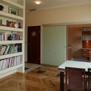Dzięki przesuwanym, matowym drzwiom, kuchnia może być albo samotną, odciętą od reszty mieszkania wyspą lub przestrzenią, która dzięki okładzinie  podłogowej, doskonale współgra ze znajdującym się obok salonem. Fot. Tomasz Markowski.