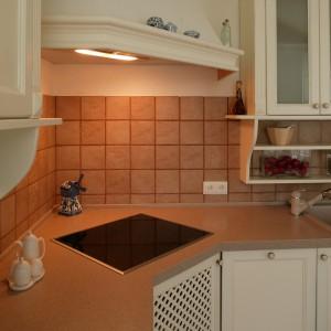 Narożnik kuchni to strefa gotowania. Wbudowana w blat płyta nie kłóci się z eleganckim wystrojem. Ciepłe światło sączące się z okapu wprowadza kameralny nastrój. Fot. Tomasz Markowski.