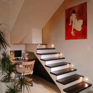 Doskonałym pomysłem zagospodarowania przestrzeni okazało się zaaranżowanie kameralnego minibiura w kąciku pod schodami. Domownicy mogą z niego skorzystać w każdej chwili. A gdy zbierze się więcej osób, do siedzenia mogą posłużyć stopnie schodów. Fot. Tomek Markowski.