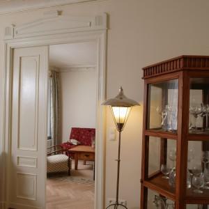 Oryginalna lampa, w stylu art déco to wynik niezłomnych poszukiwań właścicieli mieszkania. Odnaleźli ją w jednym z sopockich antykwariatów. W salonie znalazła swoje miejsce obok odnowionych sosnowych drzwi. Fot. Tomasz Markowski.