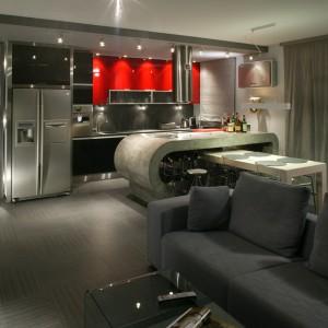 """Nieodłączną częścią salonu jest industrialna kuchnia. To obszar bardzo efektowny, nie tylko za sprawą czerwonego koloru – najmocniejszego akcentu we wnętrzu, ale także oryginalnej, """"betonowej"""" wyspy kuchennej. Fot. Tomek Markowski."""