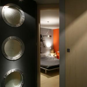 Przesuwne drzwi oddzielają łazienkę od sypialni gospodarzy. W obu pomieszczeniach dominują odcienie szarości. Ściana z bulajami jest wspólna dla łazienki i holu. Fot. Tomasz Markowski.