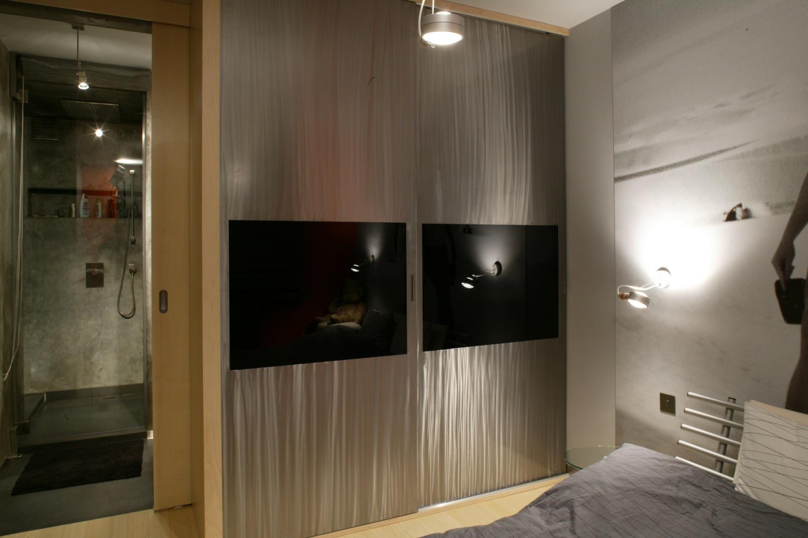 Meble zostały tu ograniczone do minimum. Oprócz łóżka znalazło się tu jeszcze tylko miejsce na robioną na zamówienie szafę ze stali szlifowanej, z wmontowanymi płaszczyznami czarnego szkła. Fot. Tomek Markowski.