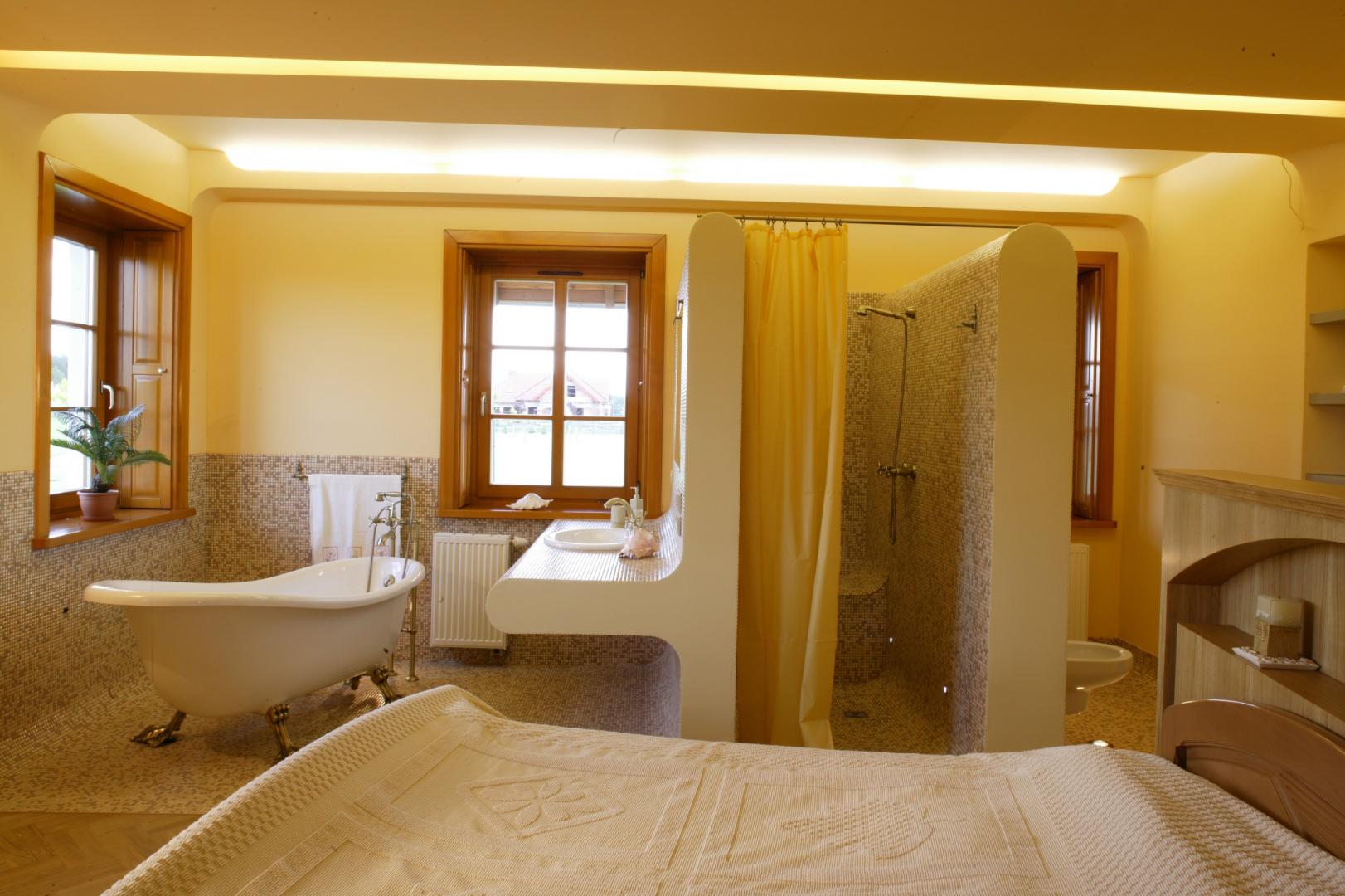 Każda strefa łazienki to osobny zakątek dostępny bezpośrednio z sypialni. Uwagę przyciąga wanna retro, ustawiona na tle stylowych okien w wewnętrznymi okiennicami. Fot. Monika Filipiuk.