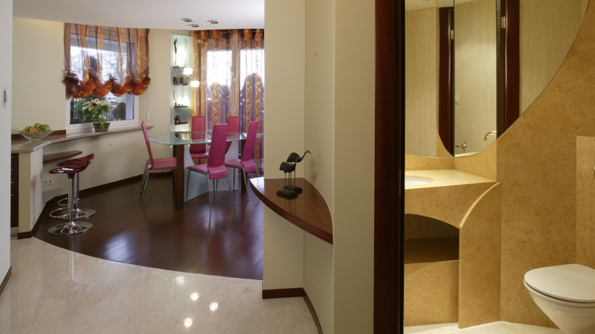 W apartamencie niewiele jest kątów prostych – łagodne łuki sprzyjają płynnemu przenikaniu przestrzeni. Widoczne są na podłodze, suficie i we wszelkich zakamarkach.