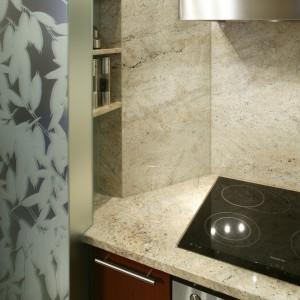 Granit, marmur i szkło - do tego zestawu materiałów pasuje wyłącznie stalowy okap. Narożna wnęka z półkami to dowód, że zagospodarowano każdy skrawek przestrzeni w niewielkiej kuchni.