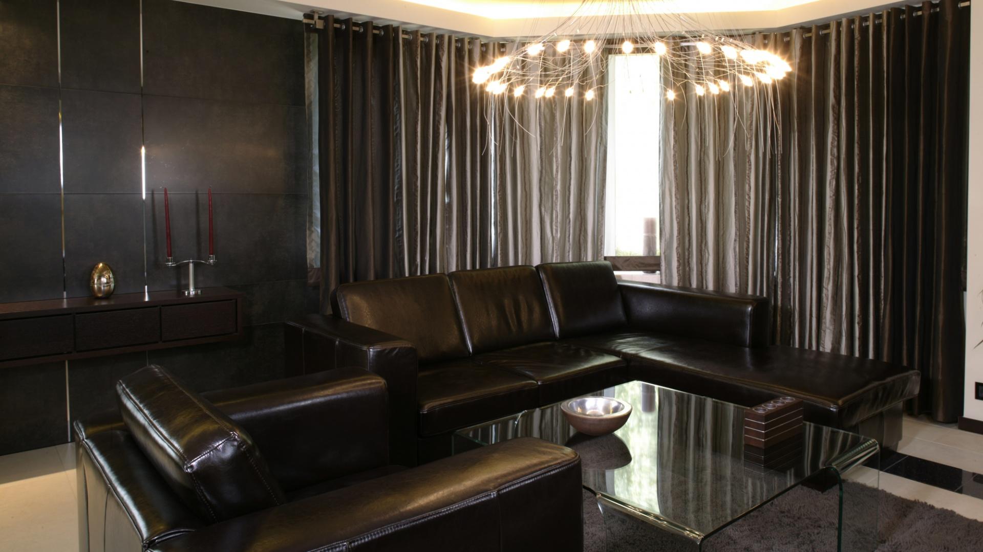 W wypoczynkowej strefie salonu stanęły skórzane kanapy w odcieniu ciemnej czekolady oraz lekki, szklany stolik do kawy. Również tutaj, ściana została wyłożona antracytowymi płytami, do których umocowano półkę z drewna wenge. Fot. Monika Filipiuk.