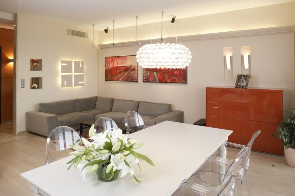 Dekoracyjne światło i mocne, czerwone akcenty – to najbardziej wyraziste elementy aranżacji salonu. Czerwień została wyrażona w postaci dyptyku autorstwa Włodzimierza Brudnika i nawiązującej kolorystycznie do niego nowoczesnej komody (Poliform). Fot. Monika Filipiuk.