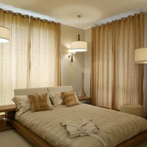 Pełna spokojnej harmonii sypialnia, z dość nietypowym i ciekawym rozwiązaniem – ustawionym na środku łóżkiem (Poliform). Przytulny klimat wnętrza to zasługa zastosowanej ciepłej kolorystyki, naturalnych materiałów (drewno, wiklina, tkanina) oraz oświetlenia. Fot. Monika Filipiuk.