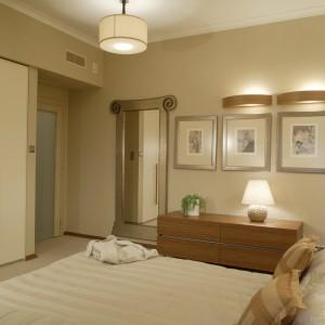 Beże i odcienie ecru to dominująca gama kolorystyczna w sypialni. Taki kolor ma subtelna tapeta, inspirowana bambusem, wełniana, pętelkowa wykładzina, abażury lamp, garderobiana szafa z otwieranymi drzwiami (Poliform) oraz narzuta na łóżku. Fot. Monika Filipiuk.
