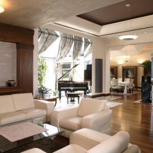 Kolorystykę salonu wyznaczają barwy drewna lapacho i marmuru, którymi wyłożono podłogę. Pięknie komponuje się z nimi kremowy komplet wypoczynkowy (Natuzzi) oraz komoda (Selva). Fot. Monika Filipiuk.