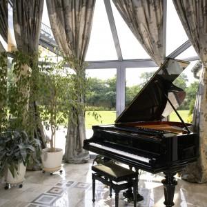Salon otwarty jest na nietypową oranżerię, miejsce wyjątkowe, z kilku powodów. Duże, załamujące się w kierunku dachu okna, dają nieograniczony dostęp światła. To idealna przestrzeń do hodowania kwiatów... i gry na fortepianie. Fot. Monika Filipiuk.
