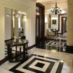 Czarny granit pojawia się na podłodze w całym domu. Ale to właśnie w holu osiąga pozycję dominującą. Ułożony w kwadraty, dodaje temu miejscu czaru pałacowych posadzek. Fot. Monika Filipiuk.