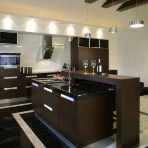 Kuchnia jest przestronna i wysoka. By osiągnąć taki efekt, architekt pozostawiła belki konstrukcyjne, które następnie zostały obudowane drewnem. Nad wyspą kuchenną, mamy więc nie tylko efektowny element dekoracyjny. Fot. Monika Filipiuk.