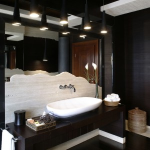 Elegancka i efektowna toaleta dla gości. W dwóch, umieszczonych naprzeciw siebie lustrach, odbijają się wszystkie elementy tego wnętrza – zarówno te matowe, nieco surowe, jak i ciepłe. Fot. Monika Filipiuk.