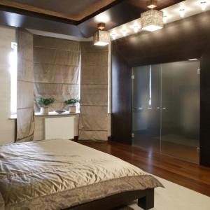 Blask narzuty na łóżku i rolet, akcentują lampy. Ich klosze również uszyto z pięknych tkanin (Volta). Szklane tafle drzwi kryją garderobę małżonków. Fot. Monika Filipiuk.