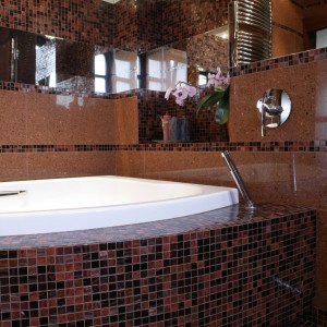 Obudowa z mozaiki utworzyła wokół wanny praktyczną półkę. Bateria o ascetycznym kształcie idealnie wpisują się w ekskluzywny klimat łazienki. Fot. Monika Filipiuk.