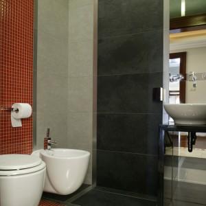Oryginalny układ płytek ceramicznych oraz elementów uzupełniających wyróżnia łazienkę. Połączenie płytek gresowych (Ceramica Venis) z czerwoną mozaiką szklaną (Villi Glass) okazało się niezwykle efektowne. Fot. Monika Filipiuk.
