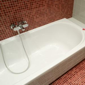 Otoczona czerwienią wanna, została obudowana szarymi płytkami. Przedłużenie obudowy służyć może jako praktyczna półka na kosmetyki i gadżety uprzyjemniające kąpiel. Fot. Monika Filipiuk.