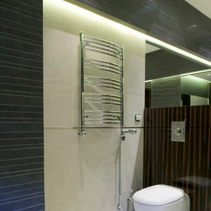 Dobudowana ścianka tworzy intymną strefę higieniczną, niewidoczną od wejścia. Znajdujący się tutaj grzejnik jest dodatkowo wyposażony w grzałkę elektryczną, pozwalającą ogrzać ręczniki lub łazienkę bez włączania centralnego ogrzewania w całym domu. Fot. Monika Filipiuk.