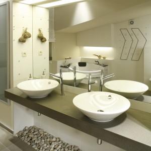 Oprócz wanny i kabiny prysznicowej, znalazło się tu także miejsce na bliźniacze umywalki (Starck), oparte na brązowym blacie z corianu i identyczne, pionowe szafki z przeszklonymi frontami. Fot. Bartosz Jarosz.