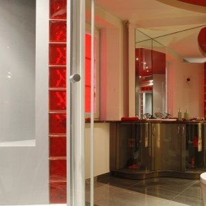 Elegancka szafka podumywalkowa i jednocześnie  toaletka wykonana została na zamówienie.  Jej bryła to kombinacja giętego, lakierowanego MDF-u oraz szkła. Lustra nad nią, ustawione pod kątem, zwiększają przestrzeń łazienki. Fot. Monika Filipiuk.