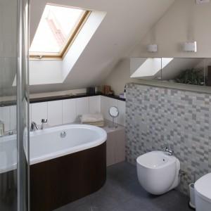 Przezroczyste ściany kabiny prysznicowej nie odbierają łazience przestrzeni ani nie przesłaniają widoku obudowanej drewnem wanny i jej starannie skomponowanego otoczenia. Na murku - dla poprawienia nastroju – można ustawić świece. Fot. Bartosz Jarosz.